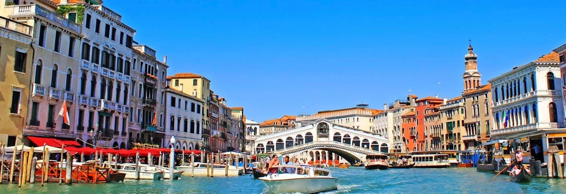 Water taxi on the Grand Canal and the Rialto Bridge at the back
