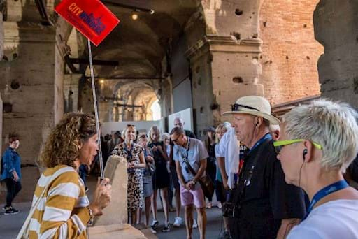 Tourists in Rome listening to their tour guide inside the Colosseum
